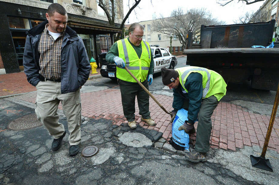 Hour Photo/Alex von Kleydorff Department of Public Works Richard Sirois and John Gardella repair a pothole in a crosswalk on Washington St in SoNo as Road Supervisor Jose Lopez keeps track of the citys potholes and assigns them to road crews