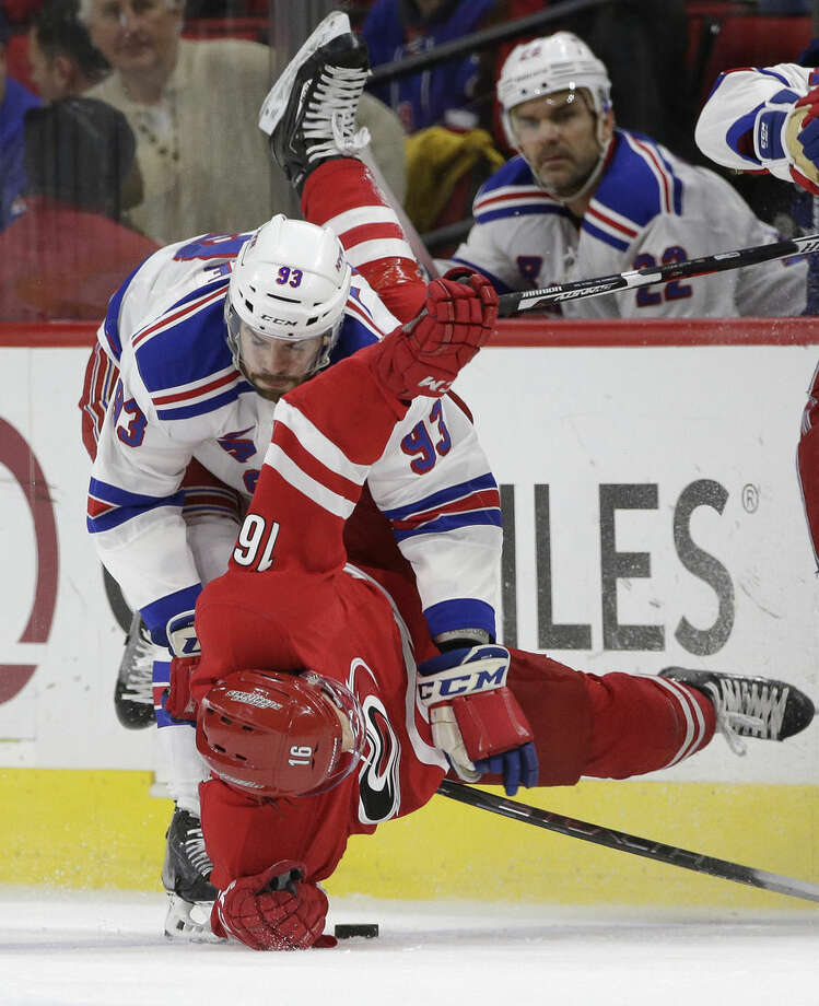 Carolina Hurricanes' Elias Lindholm (16) falls to the ice while chasing the puck with New York Rangers' Keith Yandle (93) during the first period of an NHL hockey game in Raleigh, N.C., Friday, Jan. 22, 2016. (AP Photo/Gerry Broome)