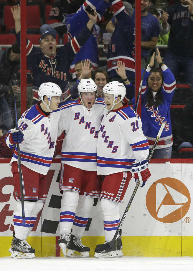 New York Rangers' J.T. Miller (10) is congratulated by Jesper Fast (19), of Sweden, and Derek Stepan (21) following Miller's second goal against the Carolina Hurricanes in the second period of an NHL hockey game in Raleigh, N.C., Friday, Jan. 22, 2016. (AP Photo/Gerry Broome)