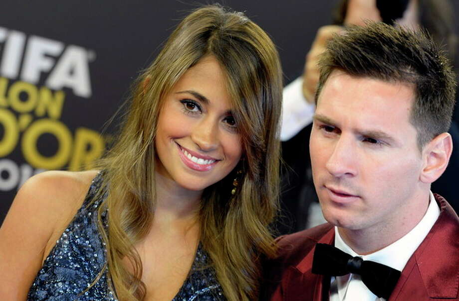 Soccer player Lionel Messi, right, of Argentina arrives with his wife Antonella, left, on the red carpet prior to the FIFA Ballon d'Or 2013 gala held at the Kongresshaus in Zurich, Switzerland, Monday, Jan. 13, 2014. (AP Photo/Keystone,Walter Bieri) / Keystone