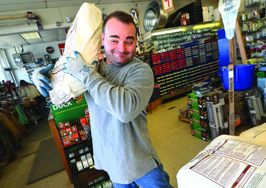 Hour Photo/Alex von KleydorffKevin McCormack lifts a bag of ice melt to bring to a customers car at Carlyn Hardware on Thursday