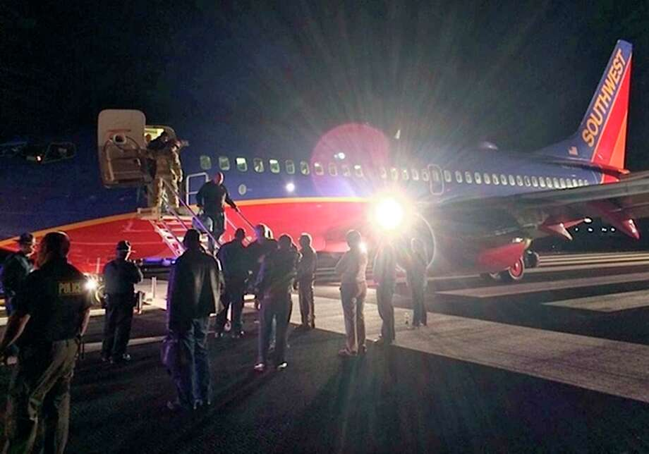 In this Sunday, Jan. 12, 2014 photo provided by Scott Schieffer, passengers exit a Southwest Airlines flight that was supposed to land at Branson Airport in Branson, Mo., but instead landed at Taney County Airport, in Hollister, Mo., that only has about half as much runway. A Southwest spokesman said all 124 passengers and five crew members were safe. (AP Photo/ Scott Schieffer) MANDATORY CREDIT / Scott Schieffer