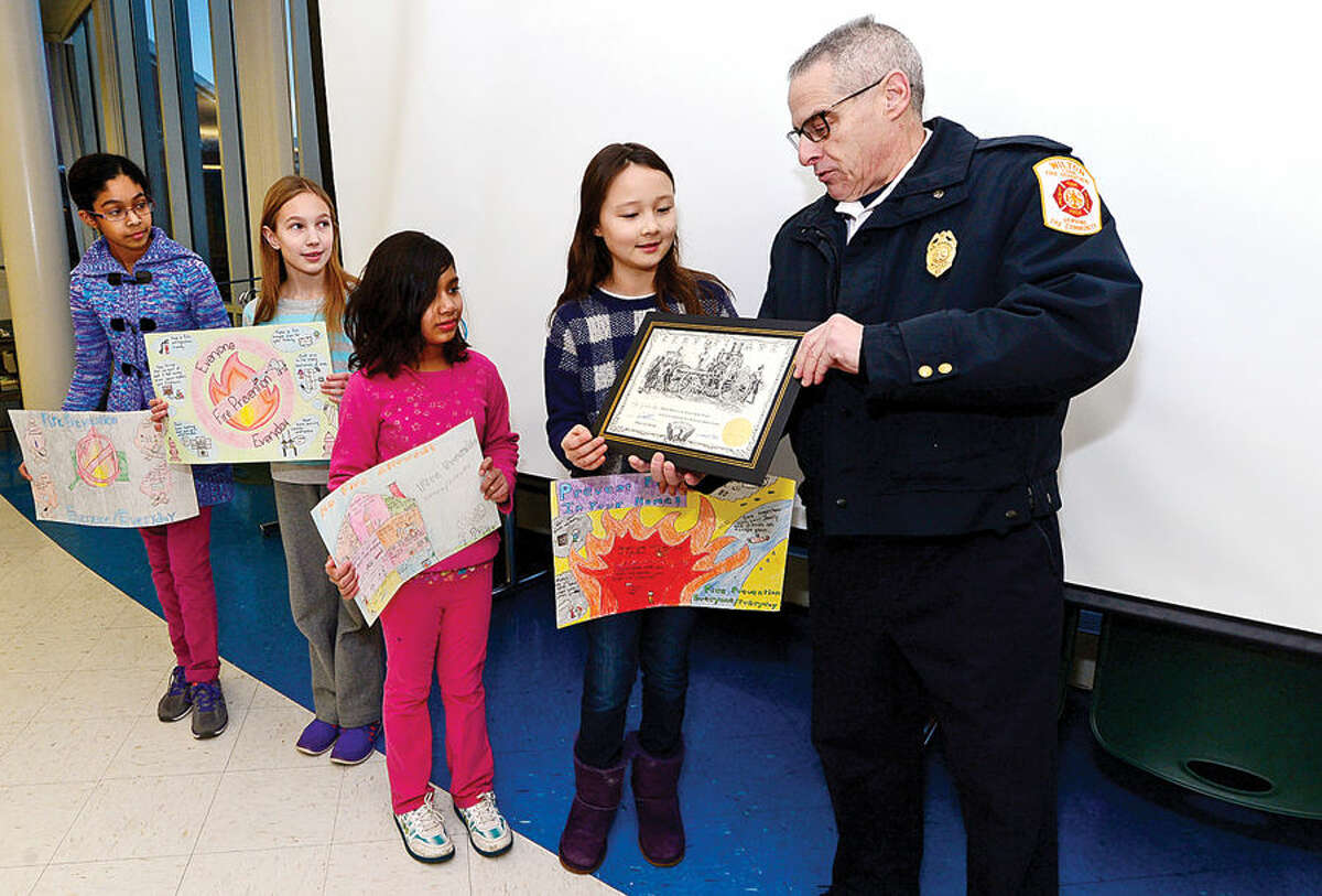 Wilton Fire Marshal David Kohn and Wilton Firefighters Local 2233 present awards to Cider Mill School students, fifth-grade runner-up Samhita Kakarlapudi, fifth-grade winner Emily Bukowski, fourth-grade runner-up Sanyam Ajitabh and fourth-grade winner Sarah Whitney, for their entries in the 2014-2015 Connecticut Fire Prevention Poster Contest Thursday.