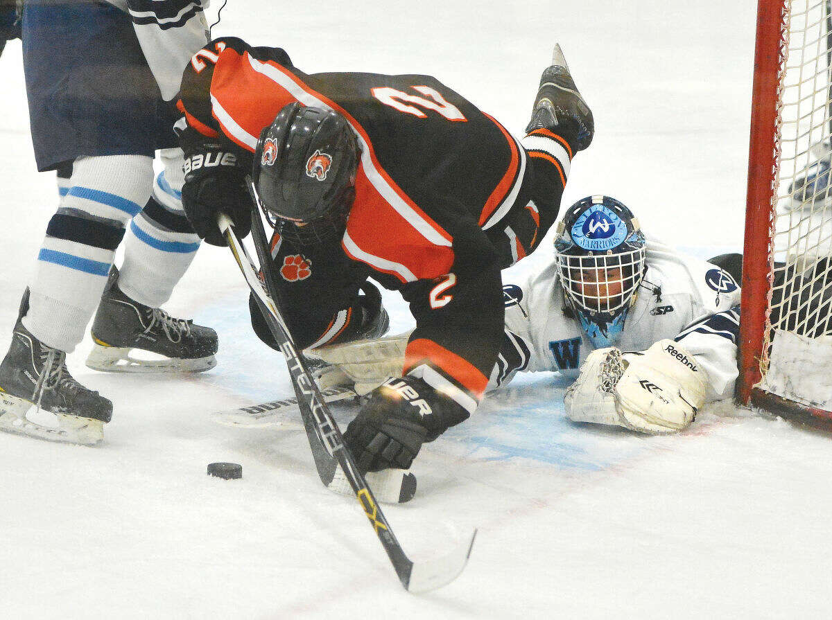 Wilton goalie Alex Sywak, right, looks for the puck near the net during Friday afternoon's matinee against archival Ridgefield.