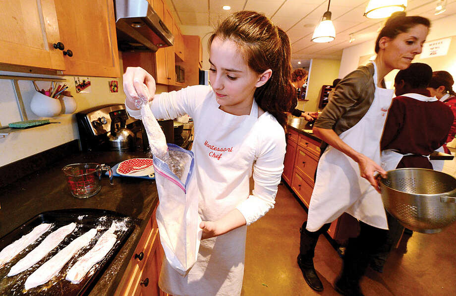 Montessori School students in the culinary arts program, including 12-year-old Amelia Heffern, prepare lunch for the school Thursday morning.