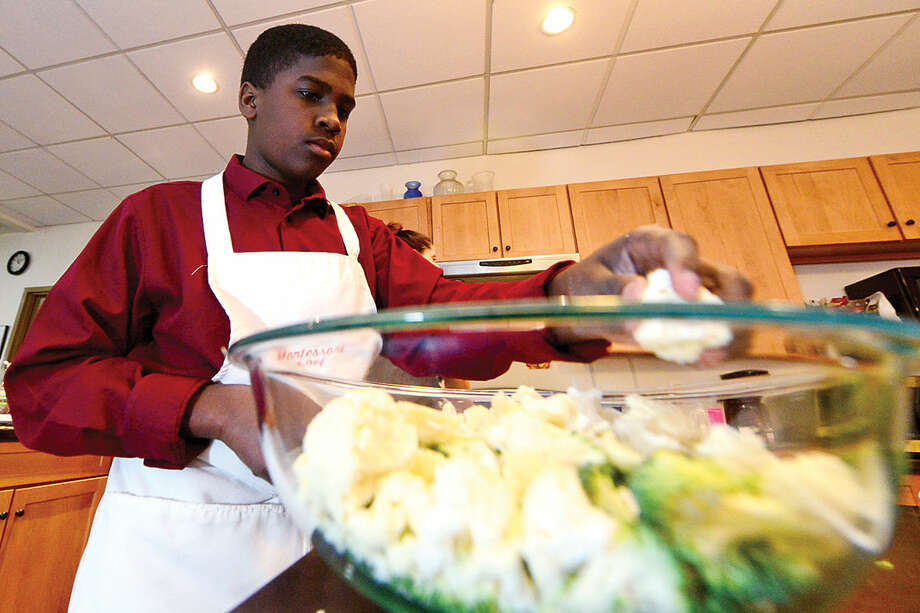 Montessori School students in the culinary arts program, including 14-year-old Michael Dubissette, prepare lunch for the school Thursday morning.
