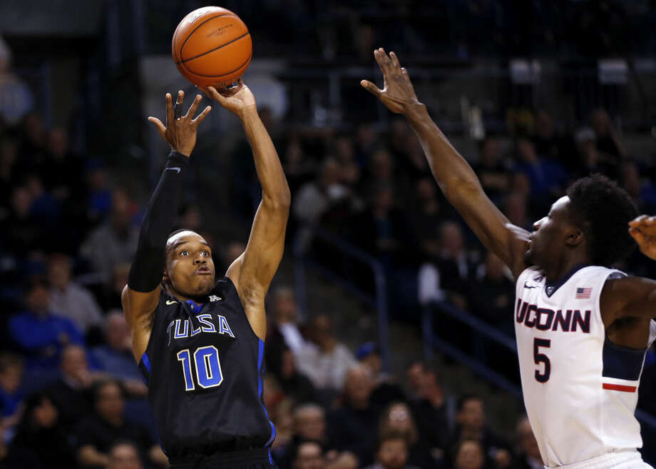 Tulsa's James Woodard (10) shoots against UConn's Daniel Hamilton (5), during Tulsa's 66-58 win in their NCAA college basketball game at the Reynolds Center in Tulsa, Okla. on Tuesday, Jan. 13, 2015. (AP Photo/Tulsa World, Cory Young)