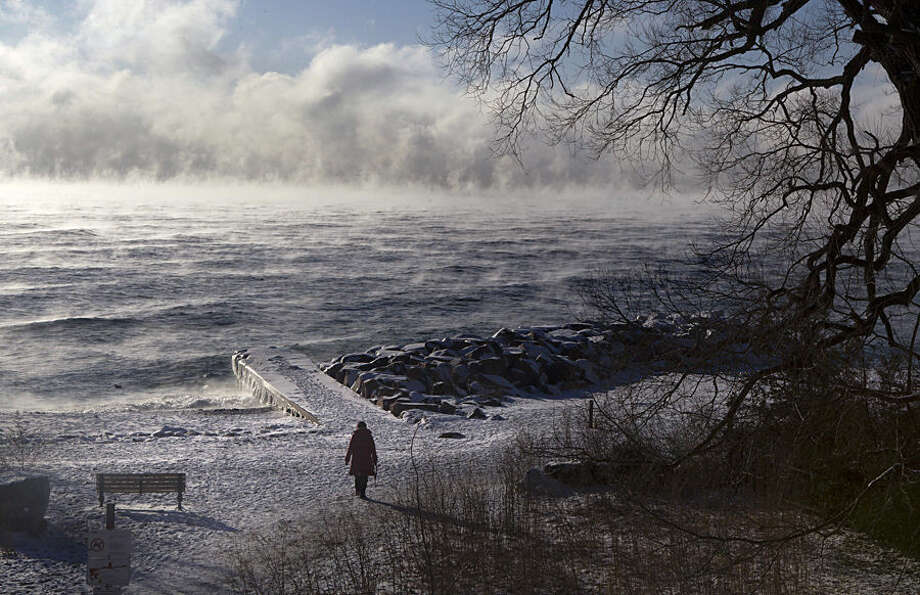 A woman walks along the beach while mist rises from a lake, Tuesday, Jan. 13, 2015, in the east end of Toronto. (AP Photo/The Canadian Press, Chris Young)