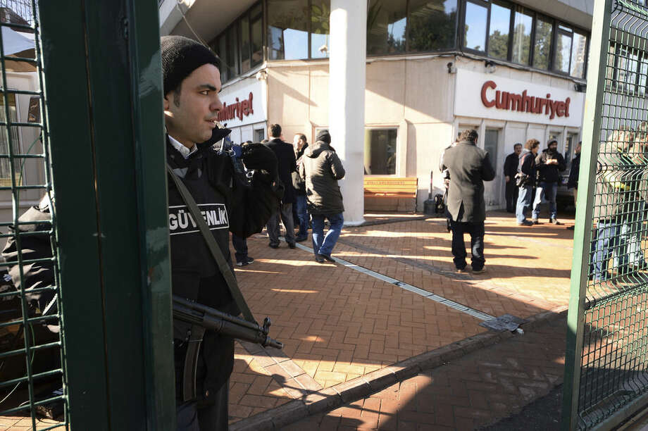 A police officer stands guard at the entrance of Cumhuriyet, the leading pro-secular Turkish newspaper, in Istanbul, Turkey, Wednesday, Jan. 14, 2015. Cumhuriyet said police stopped trucks as they left its printing center to check the paper's content after it decided to print a selection of Charlie Hebdo caricatures. Cumhuriyet said police allowed distribution of the newspaper to proceed on Wednesday after verifying that the satirical French newspaper's controversial cover featuring the Prophet Muhammad was not published. (AP Photo)