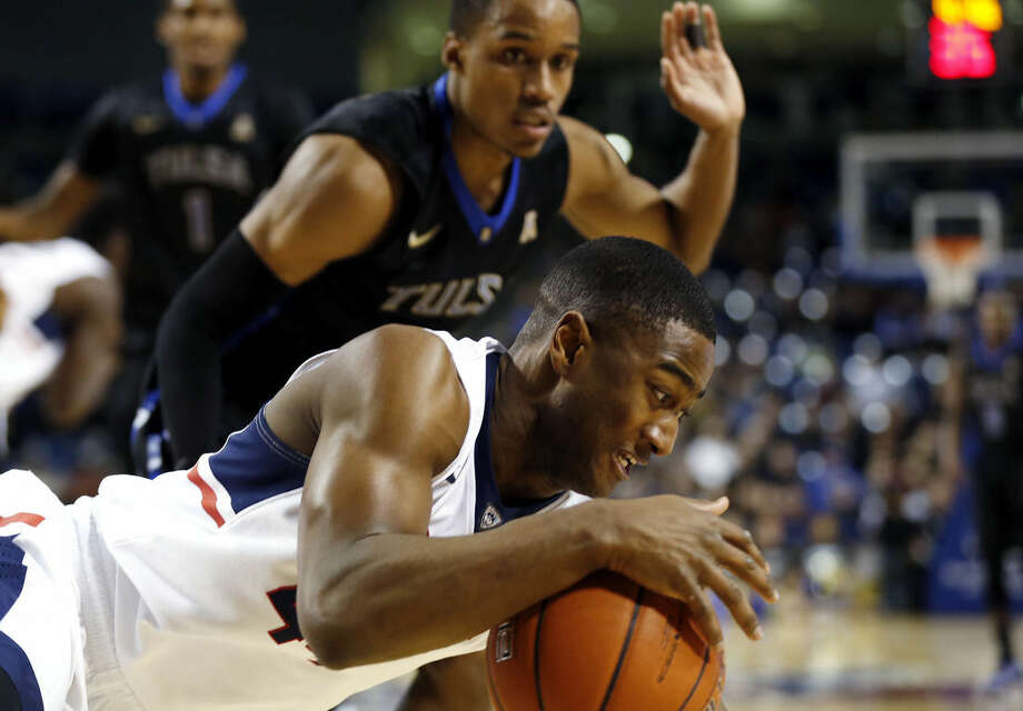 Tulsa's James Woodard, background, watches as Rodney Purvis, of UConn, falls during Tulsa's 66-58 win during an NCAA college basketball game at the Reynolds Center in Tulsa, Okla. on Tuesday, Jan. 13, 2015. (AP Photo/Tulsa World, Cory Young)