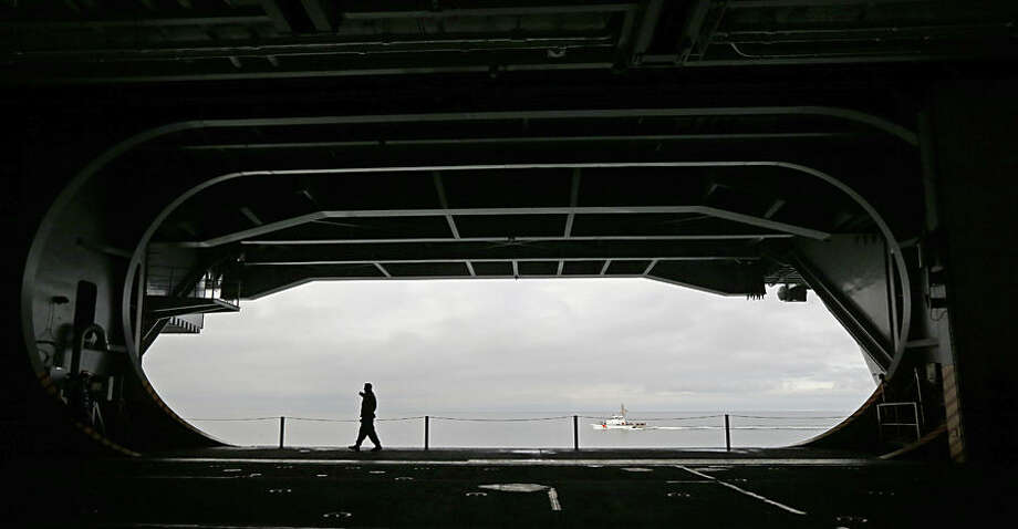 A sailor walks in front of a hanger bay door on the USS John C. Stennis Navy aircraft carrier, Monday, Jan. 12, 2015, as it moves from Naval Base Kitsap in Bremerton, Wash. The carrier sailed to Naval Magazine Indian Island, Wash., in order to take on ammunition before a training mission in the Pacific Ocean near San Diego, Calif. (AP Photo/Ted S. Warren)