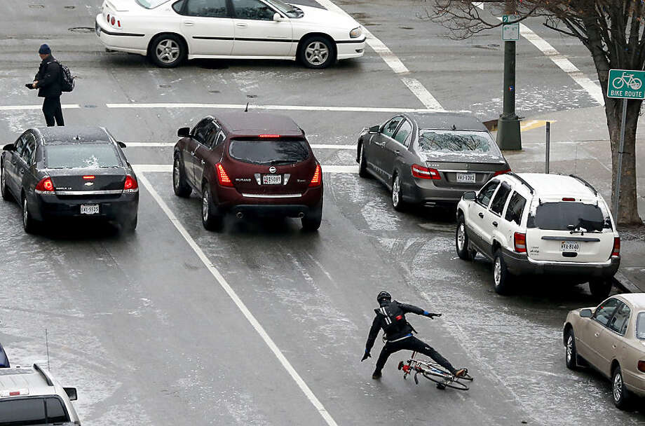 A cyclist falls as their bike slides along Grace St. during an icy commute in downtown Richmond, Va., Wednesday, Jan. 14, 2015. State transportation officials are advising motorists to be careful on Virginia roads because of icy conditions. (AP Photo/Richmond Times-Dispatch, Mark Gormus)