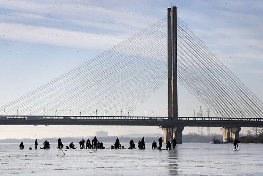 Ukrainians fish in the frozen river Dnipro in Kiev, Ukraine, Wednesday, Jan. 14, 2015. Kiev's temperature on Wednesday dropped to 7 C (44 F). (AP Photo/Efrem Lukatsky)