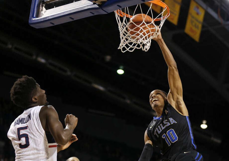 Tulsa's James Woodard (10) dunks past UConn's Daniel Hamilton during an NCAA college basketball game at the Reynolds Center in Tulsa, Okla. on Tuesday, Jan. 13, 2015. (AP Photo/Tulsa World, Cory Young)