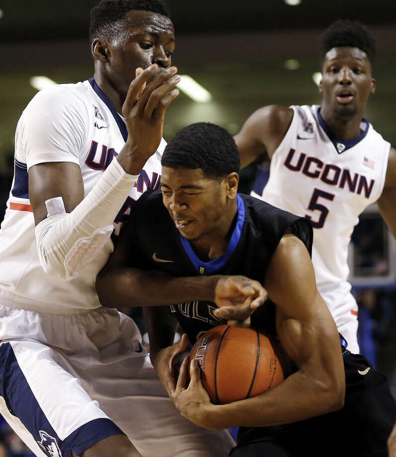 Tulsa's Shaquille Harrison, center, drives past a pair of UConn players during the Golden Hurricane's 66-58 win in an NCAA college basketball game at the Reynolds Center in Tulsa, Okla. on Tuesday, Jan. 13, 2015. (AP Photo/Tulsa World, Cory Young)