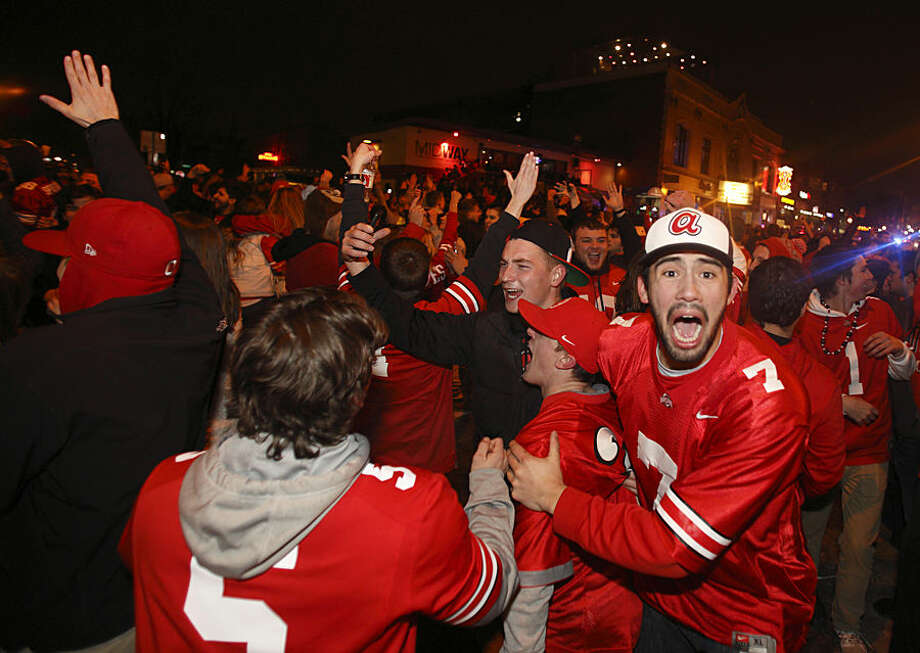 Ohio State fans block High Street in Columbus, Ohio, early Tuesday, Jan. 13, 2015, as they celebrate the Buckeye's 42-20 win over Oregon following the National Championship football game between Ohio State and Oregon. (AP Photo/Paul Vernon)