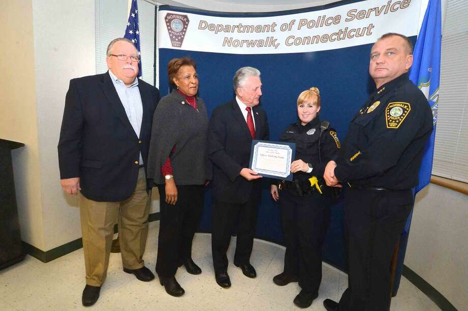 Hour Photo/Alex von Kleydorff Police Commissioners Charles Yost, Fran Collier Clemmons and Harry Rilling and Police Chief Tom Kulhawik present Officer Kimberly Prada a certificate for Officer of the Month at Norwalk Police Headquarters