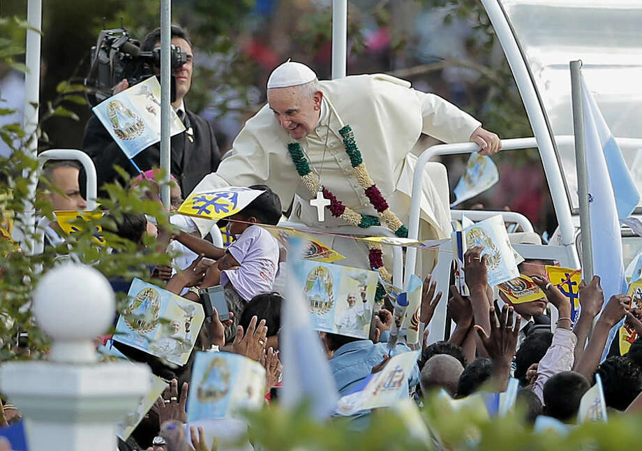 """Pope Francis stretches out his hand to touch the hands of his devotees as he arrives at the church of Our Lady of Madhu in Madhu, Sri Lanka,Wednesday, Jan. 14, 2015. Thousands of people waving the white and yellow Vatican flags were on hand to welcome Francis to the Our Lady of Madhu shrine, which is revered by both Sinhalese and Tamil Catholics, as well as Sri Lankans of other faiths. Francis also traveled to the jungles of war-torn northern Sri Lanka on Wednesday to show solidarity with the victims of the country's 25-year civil war and urge forgiveness and reconciliation """"for all the evil which this land has known."""" (AP Photo/Eranga Jayawardena)"""