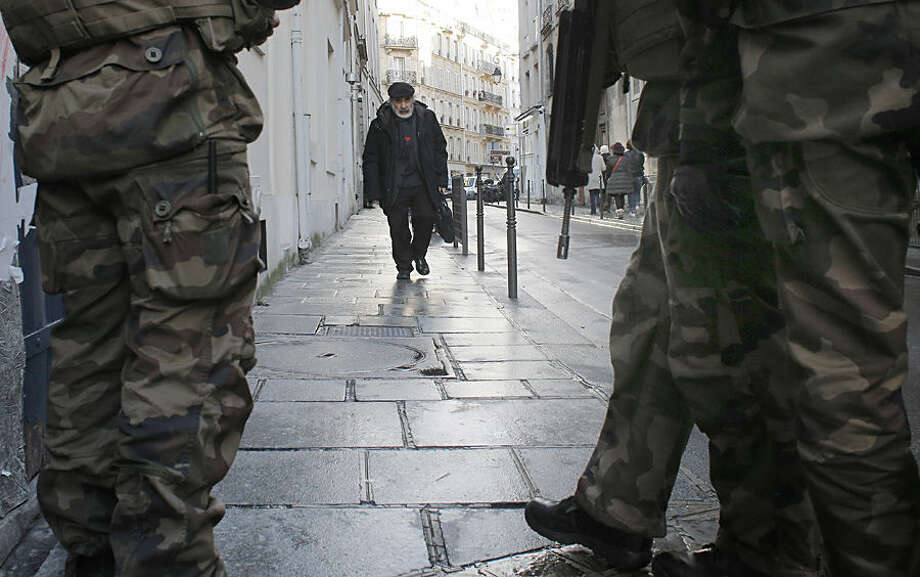 Soldiers patrol a street in Paris, Wednesday, Jan. 14, 2015. France ordered 10,000 troops into the streets Monday to protect sensitive sites — nearly half of them to guard Jewish schools — as it hunted for accomplices to the Islamic militants who left 17 people dead as they terrorized the nation. (AP Photo/Christophe Ena)