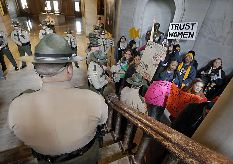 State troopers watch as abortion rights protesters stand in the Capitol as lawmakers convened the 109th General Assembly, Tuesday, Jan. 13, 2015, in Nashville, Tenn. Republican Rep. Beth Harwell of Nashville and Sen. Ron Ramsey of Blountville were re-elected as speakers of the House and Senate, while about 60 protesters outside the chambers shouted into a bullhorn, banged drums and chanted. (AP Photo/Mark Humphrey)