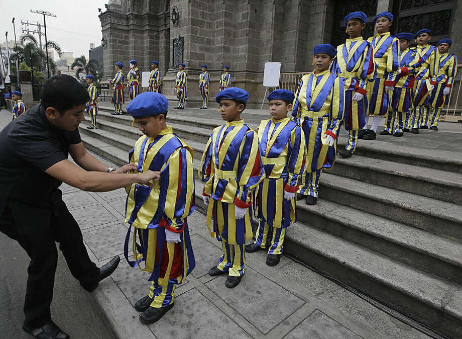A Catholic priest adjusts the uniform of boys who are dressed as Vatican Swiss guards during a rehearsal for the visit of Pope Francis outside the Manila Cathedral Wednesday, Jan. 14, 2015 in Manila, Philippines. Pope Francis arrives Thursday from Sri Lanka for a pastoral visit which is expected too draw millions of faithful where about 81-percent of the population is Catholic. (AP Photo/Bullit Marquez)