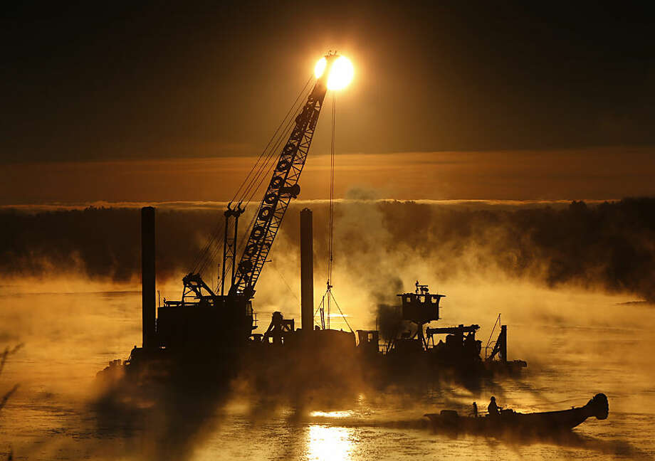 Arctic sea smoke rises on the Royal River in Yarmouth, Maine, as a worker uses a push boat to break ice forming around a dredging operation, Wednesday morning, Jan 14, 2015. The temperature at sunrise was minus 8 degrees. Sea smoke occurs when extremely cold air passes over warmer water. (AP Photo/Robert F. Bukaty)