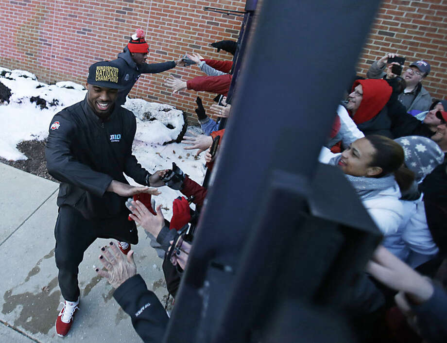 Ohio State football players high-five fans outside the Woody Hayes Athletic Center on The Ohio State University campus Tuesday, Jan. 13, 2015, in Columbus, Ohio. Ohio State defeated Oregon 42-20 in the National Championship football game. (AP Photo/Tony Dejak)