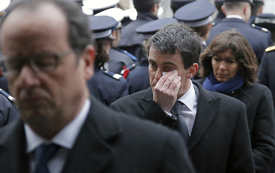 Prime Minister Manuel Valls, center, dries his tears, next to French President Francois Hollande, left, and Paris Mayor Anne Hidalgo during a ceremony to pay tribute to the three police officers killed in the attacks, in Paris, France, Tuesday, Jan. 13, 2015. Police officers Ahmed Merabet, 40, Franck Brinsolaro, 49, were killed during the attacks at Charlie Hebdo, and Clarissa Jean-Philippe killed in Montrouge last week. (AP Photo/Francois Mori, pool)