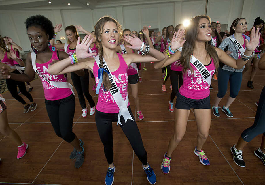 Miss Universe contestants Patricija Belousova of Lithuania, center, Abena Appiah of Ghana, left, and Claudia Tavel of Bolivia, right, participate in a Zumba Class for the contestants, Tuesday, Jan. 13, 2015 in Doral, Fla. The Miss Universe pageant will be held Jan. 25, in Miami. (AP Photo/Wilfredo Lee)