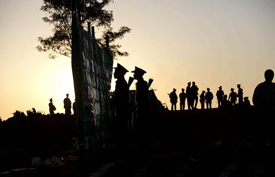 In this Monday, Jan. 12, 2015 photo, Ta'ang National Liberation army officers look at a notice board as others walk in a parade ground ahead of the 52nd Ta'ang revolution day celebrations in Mar-Wong, Ta'ang self-governing area, northern Shan state, Myanmar. Ethnic Ta'ang rebels who participate in Myanmar government's nationwide ceasefire talks continue to fight alongside the Kachin rebels against the Myanmar army in northern Shan state. (AP Photo/Gemunu Amarasinghe)