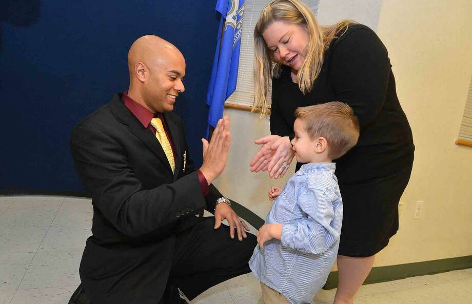 Hour Photo/Alex von Kleydorff 3 yr old Ryan with help from mom Nichole, pins the Sergeant badge on his dad Nathaniel Paulino during a promotion ceremony at Norwalk police Headquarters