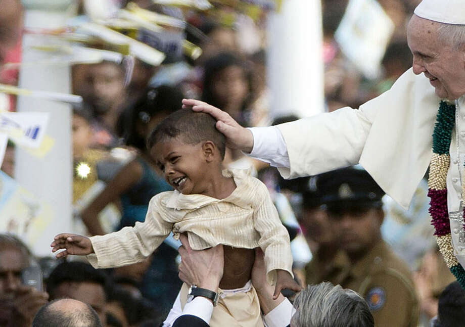 "Pope Francis blesses a child as he arrives in Madhu, Sri Lanka, Wednesday, Jan. 14, 2015. Pope Francis traveled to the jungles of war-torn northern Sri Lanka on Wednesday to show solidarity with the victims of the country's 25-year civil war and urge forgiveness and reconciliation ""for all the evil which this land has known."" (AP Photo/Alessandra Tarantino, Pool)"