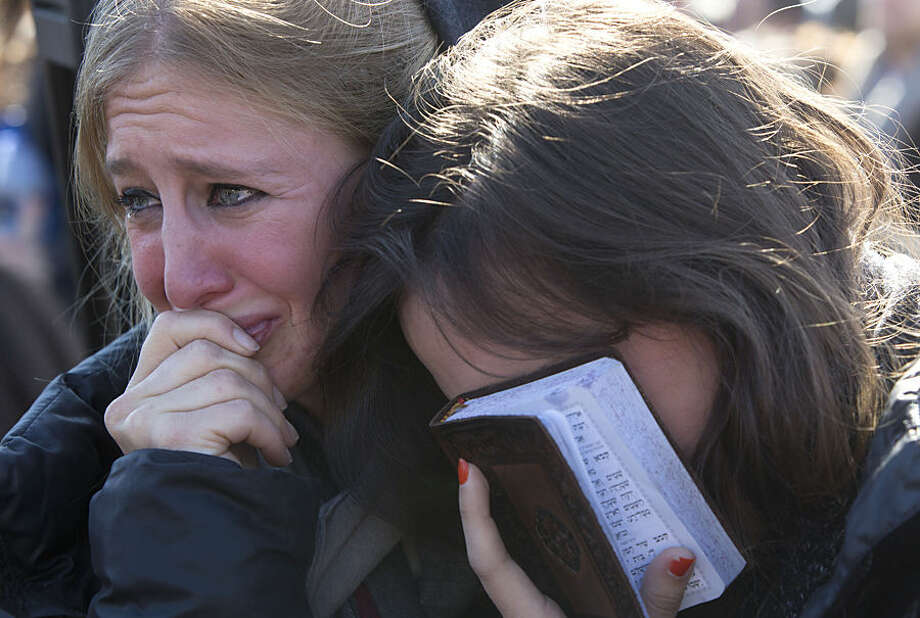 Friends and relatives of four French Jewish victims of an attack on a kosher grocery store last week in Paris, react during their funeral in Jerusalem, Tuesday, Jan. 13, 2015. Thousands of mourners joined Israeli leaders and the families of the four Jewish victims of a Paris terror attack on a kosher supermarket for an emotional funeral procession on Tuesday, reflecting the deep sense of connection and concern in Israel over the safety of fellow Jews in Europe. (AP Photo/Sebastian Scheiner)