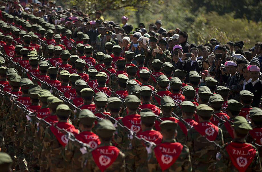 In this Monday, Jan. 12, 2015, photo, Ta'ang National Liberation Army officers march as civilians take photos with their mobile phones during a function to mark the 52nd Ta'ang revolution day in Mar-Wong, Ta'ang self-governing area, northern Shan state, Myanmar. Ethnic Ta'ang rebels who participate in Myanmar government's nationwide ceasefire talks continue to fight alongside the Kachin rebels against the Myanmar army in northern Shan state. (AP Photo/Gemunu Amarasinghe)