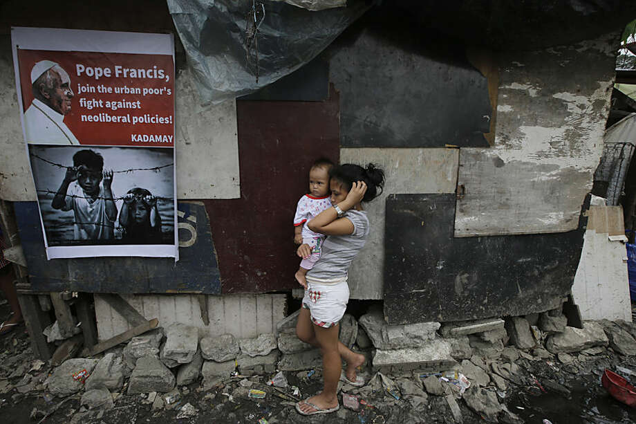 Menchie Dela Rosa, 12, carries her 10-month-old cousin Shanil beside a message for Pope Francis posted on a shanty at the garbage dumpsite of Payatas to celebrate Thursday's visit of Pope Francis Tuesday, Jan. 13, 2015 at suburban Quezon city northeast of Manila, Philippines. Pope Francis is embarking on a five-day visit to the only predominantly Catholic nation in Asia Jan. 15-19 and is expected to draw hundreds of thousands of the Filipino faithful. In their statement, the residents are hoping for Pope Francis to take notice of their plight when he meets President Benigno Aquino III. (AP Photo/Bullit Marquez)