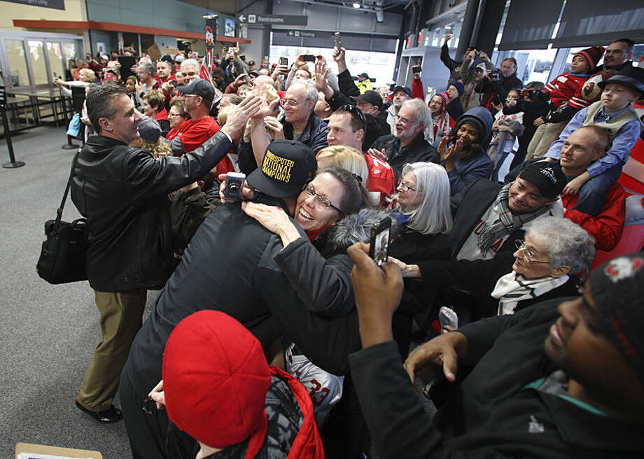 Ohio State football coach Urban Meyer, left, greets fans as he and his team arrive at Rickenbacker International Airport in Groveport, Ohio, Tuesday, Jan. 13, 2015, following a National Championship win over Oregon in Dallas, Texas. (AP Photo/Paul Vernon)