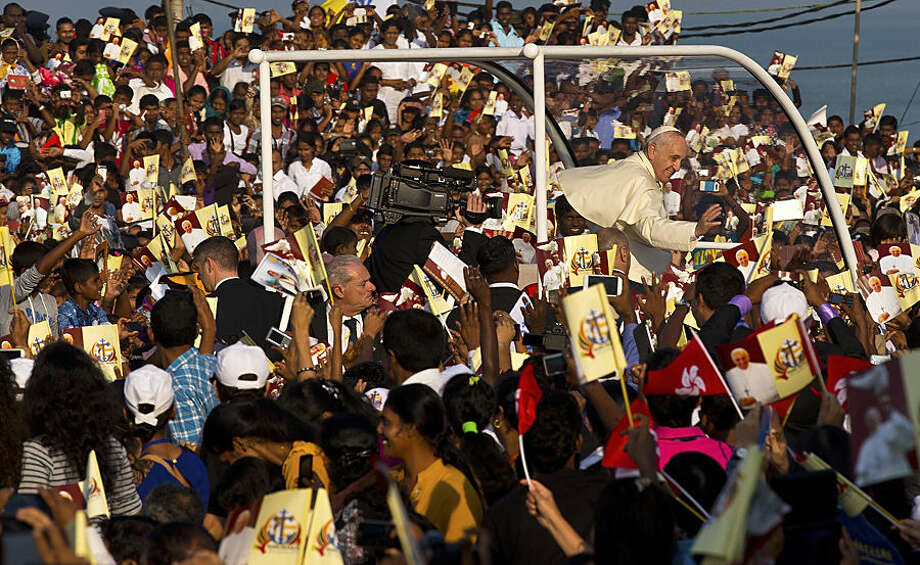 Pope Francis waves to the crowd as he arrives to hold a mass at Colombo's seafront Galle Face Green for the canonization ceremony of Joseph Vaz, Wednesday, Jan. 14, 2015. Francis declared Vaz a saint at the start of the service. The church considers Vaz a great model for today's faithful, ministering to the faithful of both Sri Lanka's ethnic groups and putting himself at great risk to spread the faith. (AP Photo/Saurabh Das)