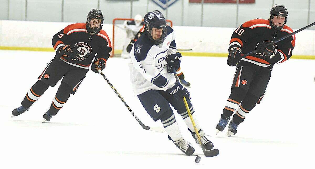 Hour photo/John Nash - Staplese-Weston-Shelton co-op skater Evan Mancini, center, skates the puck up the ice as two Ridgefield players chase during Monday's game at the Milford Ice Pavilion.