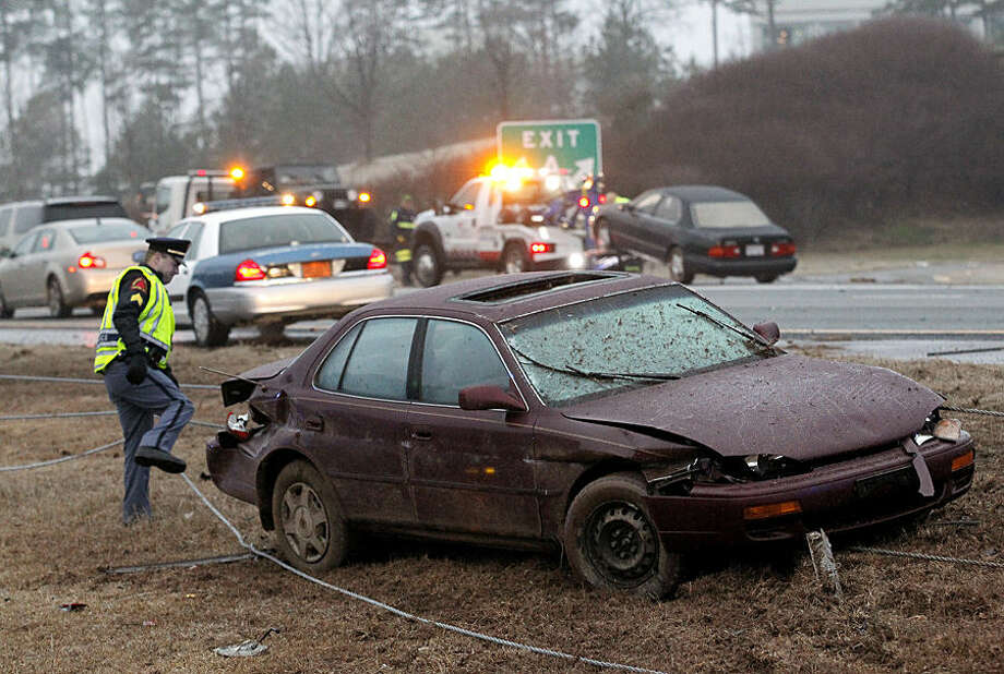 A police officer checks on a wrecked car, while two other vehicles are carted off by wreckers in the background, along westbound Interstate 540 at the Glenwood Ave. interchange, Wednesday, Jan. 14, 2015, in Raleigh, N.C. Some wrecks are being reported as freezing drizzle has fallen across much of central and eastern North Carolina.(AP Photo/The News & Observer, Chris Seward) MANDATORY CREDIT