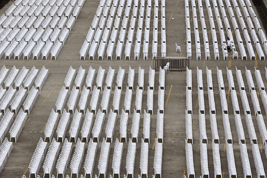 A Filipino worker arranges chairs at a venue for people to meet Pope Francis in suburban Pasay, south of Manila, Philippines on Wednesday, Jan. 14, 2015. Pope Francis arrives Thursday from Sri Lanka for a pastoral visit which is expected to draw millions of faithful where about 81-percent of the population is Catholic. (AP Photo/Aaron Favila)