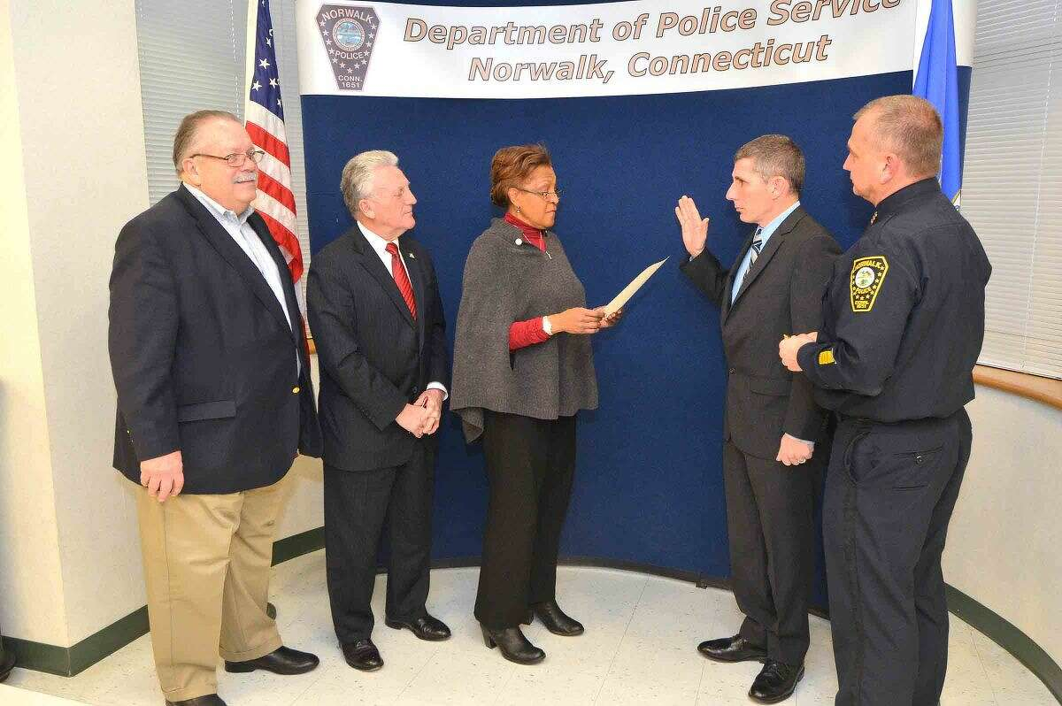 Hour Photo/Alex von Kleydorff Police Commissioners Charles Yost, Fran Collier Clemmons and Harry Rilling swear in James Mosher as Sergeant at Norwalk Police Headquarters