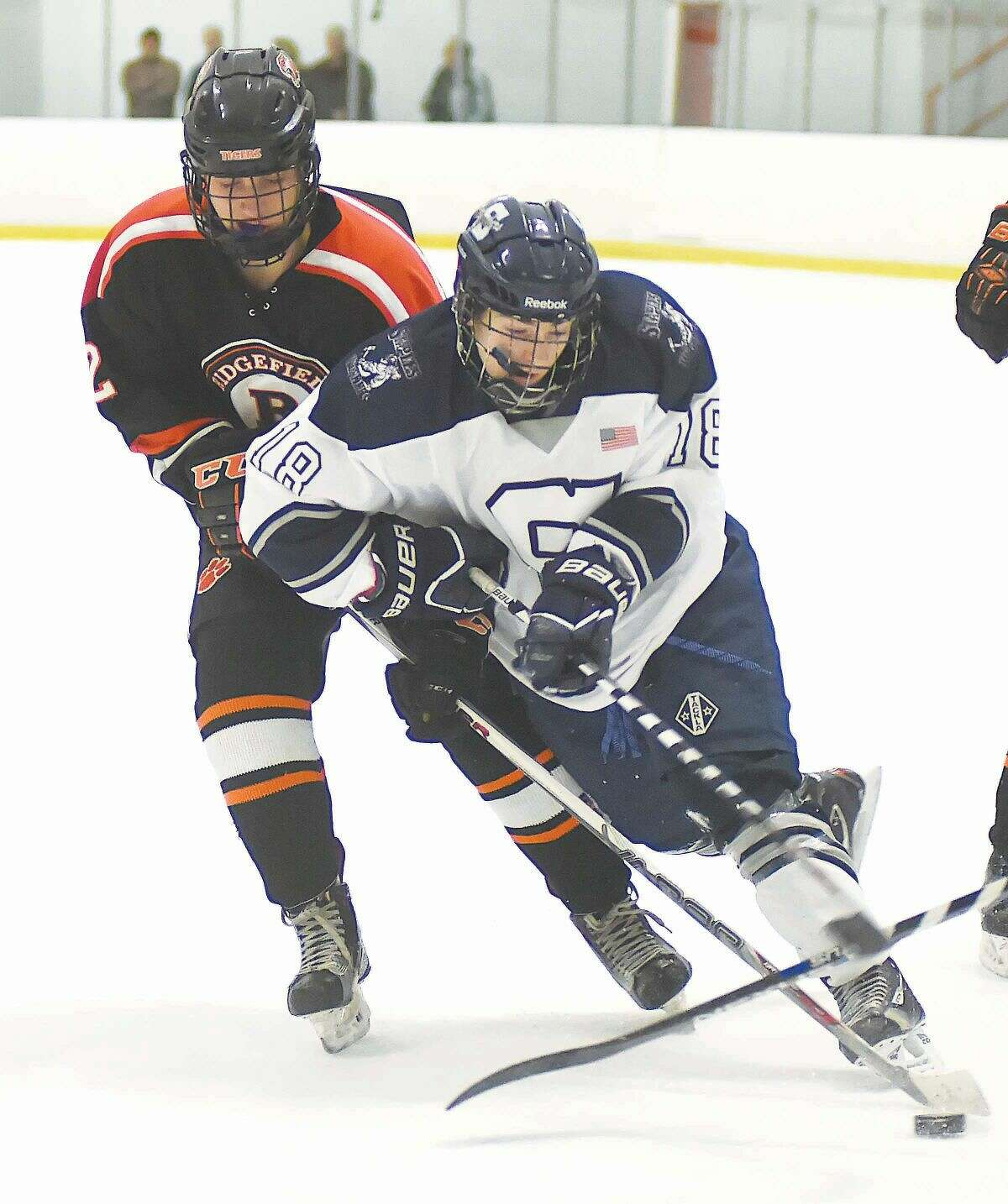 Hour photo/John Nash - Staples-Weston-Shelton co-op skater Ryan Purgay, front, controls the puck in front of a Ridgefield player during Monday's hockey game at the Milford Ice Pavilion.