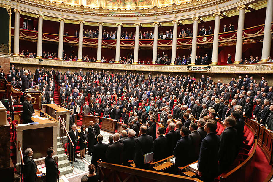 Members of the French government and deputies stand as they observe a minute of silence in homage of the 17 victims of last week terrorist attacks, at the French national Assembly in Paris, Tuesday Jan. 13, 2015. (AP Photo/Remy de la Mauviniere)