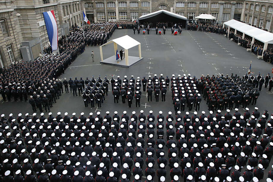 French President Francois Hollande delivers his speech, at left, during a ceremony to pay tribute to the three police officers killed in the attacks, in Paris, France, Tuesday, Jan. 13, 2015. Police officers Ahmed Merabet, 40, Franck Brinsolaro, 49, were killed during the attacks at Charlie Hebdo, and Clarissa Jean-Philippe killed in Montrouge last week. (AP Photo/Francois Mori, pool)