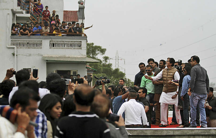 "Indians watch as Bollywood actor Amitabh Bachchan, in brown jacket, flies a kite during the kite festival in Ahmadabad, India, Wednesday, Jan. 14, 2015. Bollywood actors Dhanush and Akshra Hasan accompanied Bachchan to promote their upcoming movie ""Shamitabh"". (AP Photo/Ajit Solanki)"