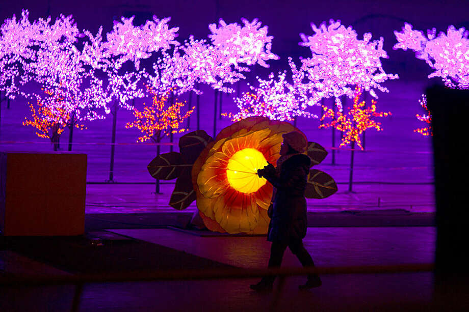 A woman walks past lights decoration set up as part of an ice carvings festival held inside the Worker's Stadium in Beijing, Wednesday, Jan. 14, 2015. (AP Photo/Ng Han Guan)