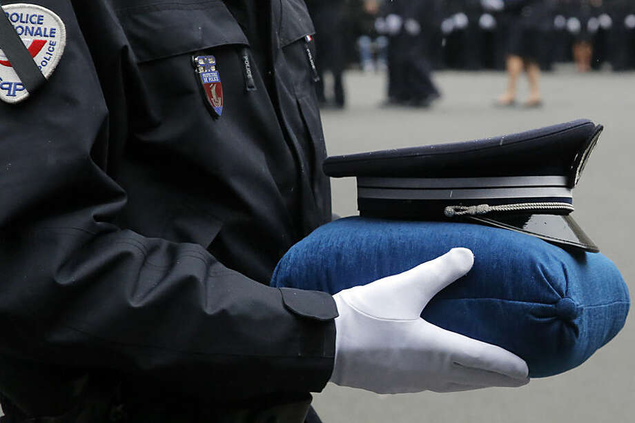 A French police officer holds the hat of late police officer Ahmed Merabet during a ceremony to pay tribute to the three police officers killed in the attacks, in Paris, France, Tuesday, Jan. 13, 2015. Police officers Ahmed Merabet, 40, Franck Brinsolaro, 49, were killed during the attacks at Charlie Hebdo, and Clarissa Jean-Philippe killed in Montrouge last week. (AP Photo/Francois Mori, pool)