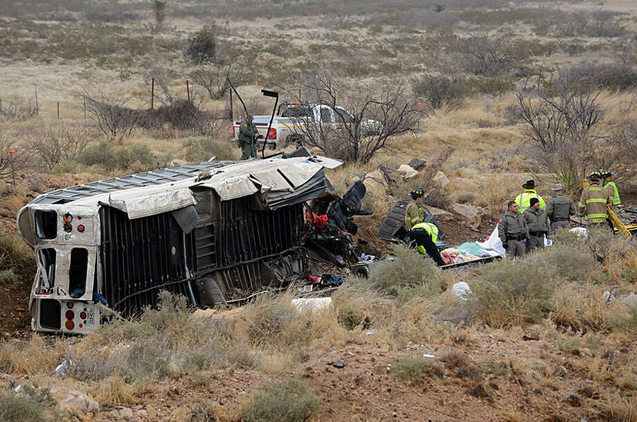 Officials investigate the scene of a prison transport bus crash in Penwell, Texas, Wednesday, Jan. 14, 2015. Law enforcement officials said the bus carrying prisoners and corrections officers fell from an overpass in West Texas and crashed onto train tracks below, killing an unspecified number of people. (AP Photo/The Odessa American, Mark Sterkel)