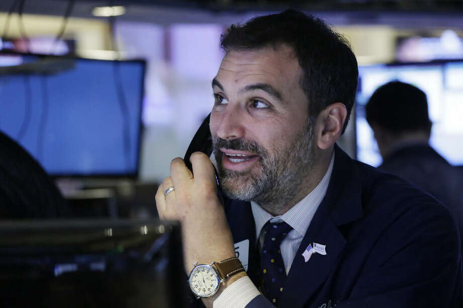 A trader smiles as he follows prices before the opening bell at the New York Stock Exchange, Friday, Jan. 22, 2016. (AP Photo/Mark Lennihan)
