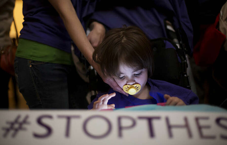 "Rebecca Spinelli touches the face of her daughter McKenzie, 4, who has mitochondrial disease, as she holds a sign reading ""stop the seizures"" at a news conference on House Bill 1 at the state Capitol, Tuesday, Jan. 13, 2015, in Atlanta. Republican state Rep. Allen Peake announced Friday that he would scale back planned legislation on the bill, which would have regulated use and production of medical cannabis oil to treat certain medical conditions in Georgia, to now giving immunity to people possessing the oil purchased in other states. Some families remain worried about being arrested with the oil while traveling across state lines. (AP Photo/David Goldman)"